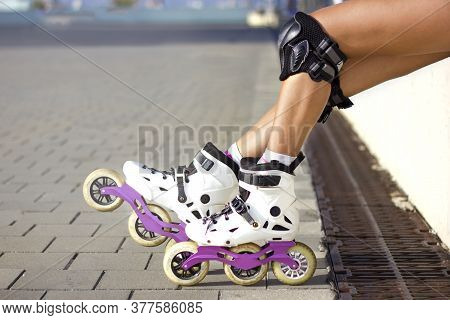 Close Up Photo Of Woman's Body Part. Legs Wearing Cute White And Pink Inline Roller Blades And Prote