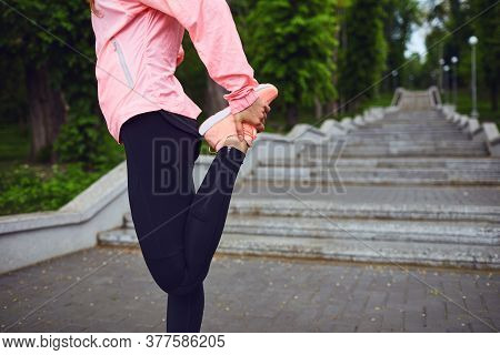 Young Jogger Stretching Her Legs After Training Outdoors. In Park.