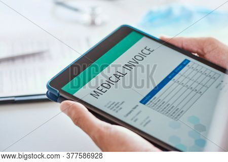 closeup of a caucasian doctor man, at his office desk, checking a medical invoice in a digital tablet