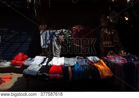 Kathmandu, Nepal - June 17, 2019: Selling clothes on street market, Sun is shining on sellers stall, Local daily life