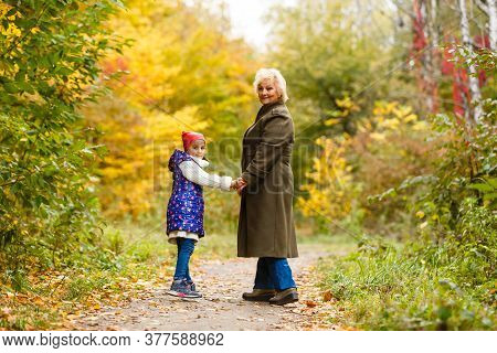 Happy Senior Lady And A Little Toddler Girl, Grandmother And Granddaughter, Enjoying A Walk In The P