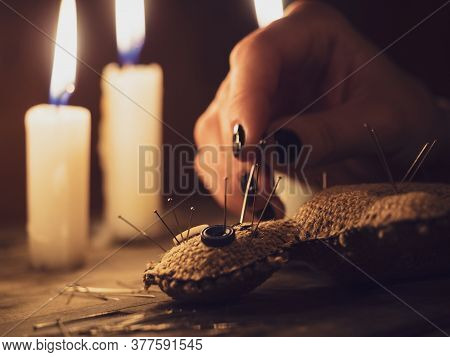A Girl Pierces A Voodoo Doll With Needles, Close-up. Esoteric And Occult Rituals On A Wooden Table I