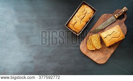 Two Freshly Baked Homemade Pumpkin Bread Loaves In Vintage Pans With Knife Over Dark Background. Ima