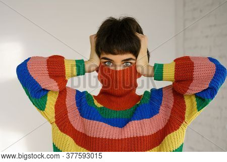 A Young Woman In A Bright Multicolored Rainbow Sweater Hides Her Face And Covers Her Ears With Her H