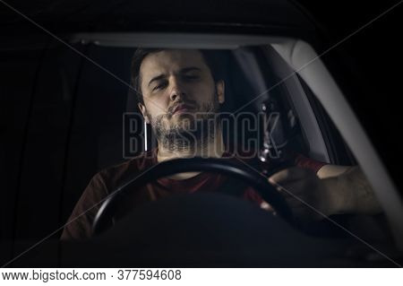A Young Bearded Man Drives A Car Holding A Bottle Of Beer In His Hand. Drunk Driving On Highways At