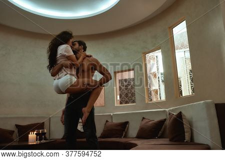 Young Sexy Man Holding His Girlfriend And Kissing Before Having Sex. Candles And Glasses Of Wine On