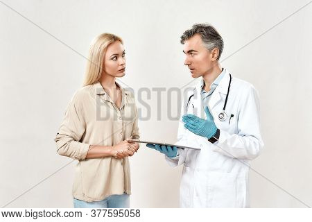 Doctor And Patient. Professional Male Doctor In Medical Uniform Using Digital Tablet And Talking Wit
