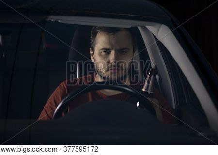 A Drunk Driver Drives A Car Holding A Bottle Of Beer In His Hand. Drunk Driving On Highways At Night