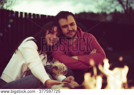 Toned Sepia Portrait Of Happy Lovely Couple Sitting By Fire On Nature. On Autumn Night. Relaxing Nea
