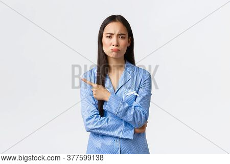 Upset Gloomy Asian Girl In Blue Pajamas Grimacing Disappointed And Sad, Showing Something Bad, Point