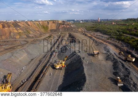Excavator And Heavy Mining Dump Trucks In A Limestone Quarry, Loading Of Stone Ore, Industrial Panor