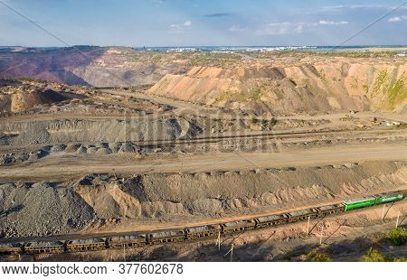 Cargo Train Carrying Iron Ore On The Opencast Mining Quarry Aerial View.