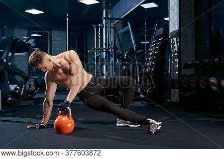 Muscular Caucasian Shirtless Man Training On Floor In Sports Club. Close Up Of Young Sportsman In Gl