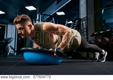 Muscular Caucasian Man Training On Floor Using Balance Half Ball In Sports Club. Close Up Of Young S