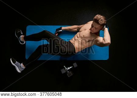 Muscular Caucasian Man Training Abs On Floor In Sports Club. From Above View Of Handsome Young Sport