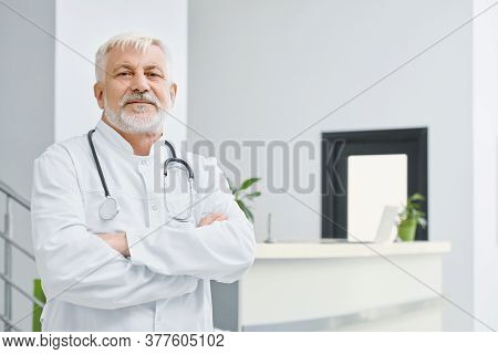 Portrait Of Eldery Caucasian Male Doctor In White Lab Coat. Selective Focus Of Professional Therapis