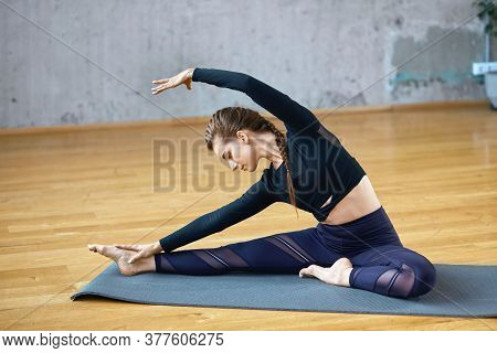 Side View Of Young Fitnesswoman In Sportswear Doing Yoga Side Bending Exercise On Gray Mat, Practici