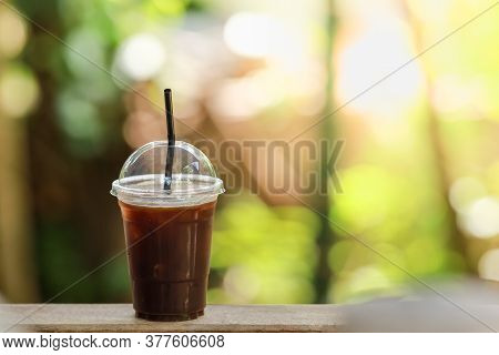 Closeup Of Takeaway Plastic Cup Of Iced Black Coffee Americano On Wooden Table With Copy Space.