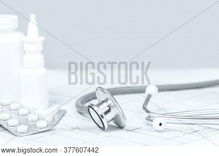Medical Grey Monochrome Background. White Tablets Pills Jars With Stethoscope. Cardio Ecg Heart Rhyt