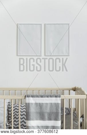 Two White Empty Wall Frames Above Infant Baby Cot Bed With Gray Blanket