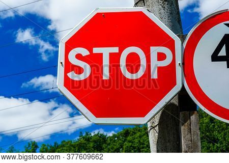 Stop Sign On Post At Roadside Against Blue Sky