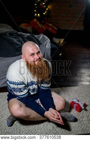 A Man With A Long Red Beard Sits On The Floor Without Pants In A Winter Sweater. Man Is Holding A Wr