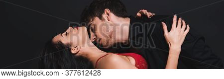 Panoramic Crop Of Passionate Man Kissing Neck Of Seductive Woman In Red Bra Isolated On Black