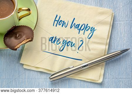 How happy are you? Handwriting on a napkin with a cup of coffee. Happiness, mindset and personal development concept.