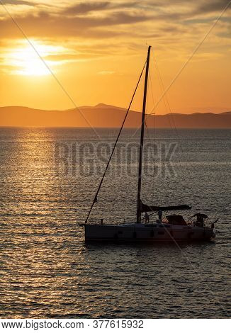 Sailing At Sunset, Boat On Calm Sea And Orange Sky Background,