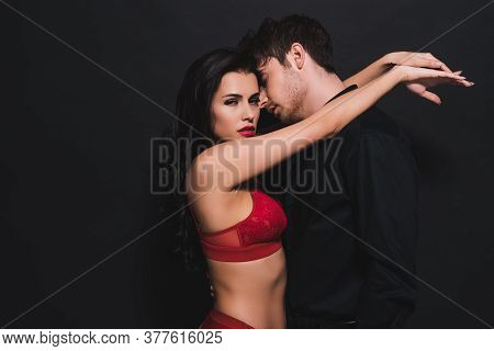 Sexy Woman In Red Bra And Panties Hugging Handsome Man Isolated On Black