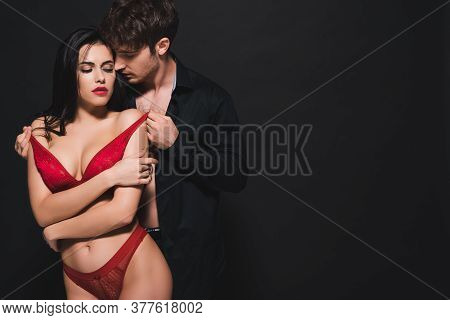 Passionate Man Touching Red Bra Of Seductive Girl On Black
