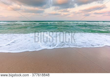 Cloudy Sunset Sea Side. Waves Running The Sandy Beach. Changing Windy Weather In Evening Light