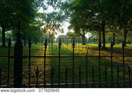Long Shadows Through Wrought Iron Fence Surrounding La Fayette Park With Lens Flare Aged Photo Effec
