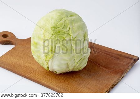 White Background. No Isolation. Head Of Fresh Cabbage On A Cutting Board. Close-up