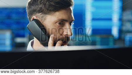 Portrait Of Male Stock Trader Operating At Her Workstation And Talking On Phone Background Of Multip