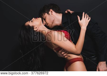 Passionate Man Kissing Neck Of Seductive Woman In Red Bra Isolated On Black