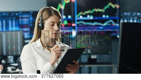 Female Stock Trader Working At Stock Exchange Office Using Headset And Digital Tablet Computer On Ba