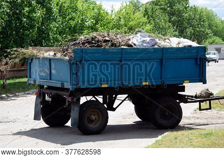 Cleaning Dry Branches And Grass On City Streets Loading Into Truck Trailer. Cleaning Dry Leaves Trac