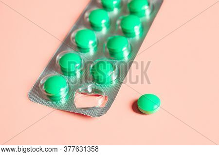 Blister Of Green Pills And Separately One Pill On A Pink Background. Concept Of Starting A Course Of