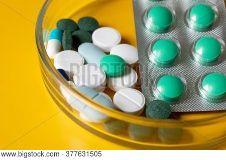 White And Blue Tablets And Pills In A Petri Dish On A Yellow Background.