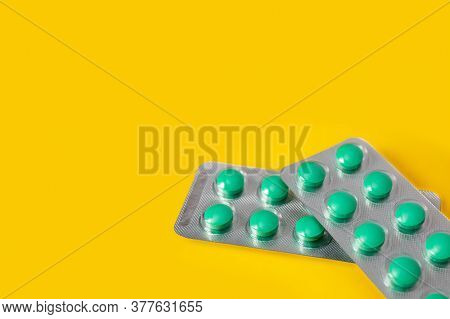 Two Blisters Of Green Pills On A Yellow Background.