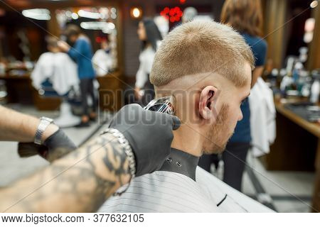 Close Up Shot Of A Young Man Visiting Barbershop And Getting New Trendy Haircut. Barber Working With
