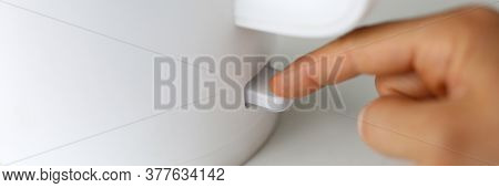 Close-up Of Person Pressing Knob On Electrical Kettle With Finger. Power Switch On. Warm Water For T