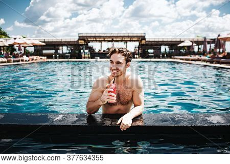 Young Hot Man Resting At Swimpool. Closer View Of Attractive Handsome Well-built Guy Drinking Cockta
