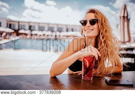 Young Hot Woman Resting At Swimpool. Gorgeous Girl Sitting Alone At Bar And Enjoying Drinking Cockta