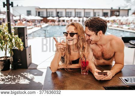 Young Hot Couple Resting At Swimpool. Woman And Man Sit At Bar And Drink Cocktails. Girl Point To Si