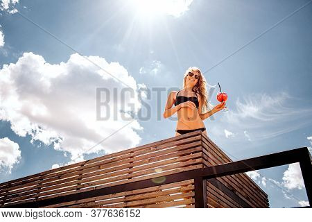 Young Hot Woman Resting Alone. Low View Of Slim Well-built Girl In Black Swimsuit Posing On Camera W