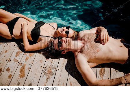 Young Hot Couple Resting Together. Side View Of Cheerful Man And Woman Lying At Swimming Pool And En