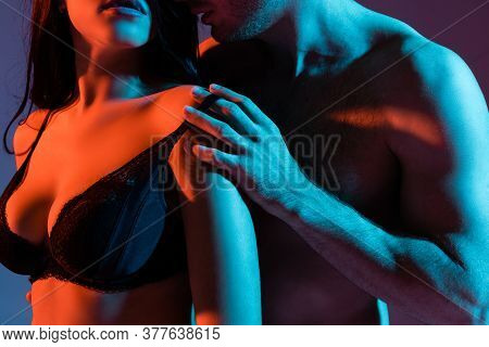 Cropped View Of Shirtless Man Touching Bra Of Sexy Woman On Purple