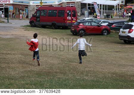 2 Boys Running Downhill To A Fair In Weymouth, Dorset In The Uk, Taken On The 30th July 2018